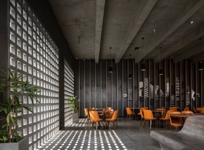 Imagem mostra um ambiente com cobogó. Em segundo plano cadeiras e mesas