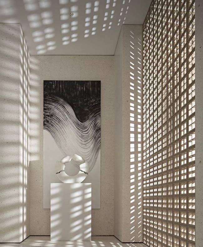 Imagem mostra um hall com cobogó da mesma cor da parede branca