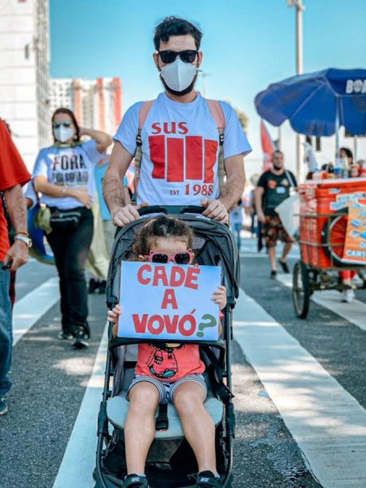 A imagem mostra uma menina pequena no carrinho de bebê segurando um cartaz onde se lê