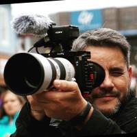 A imagem mostra o repórter fotográfico mikael fox em ação, com a câmera na mão