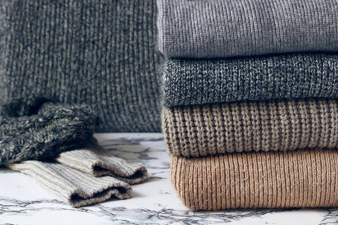 stack of cozy knitted sweaters on wooden background. Autumn-wint