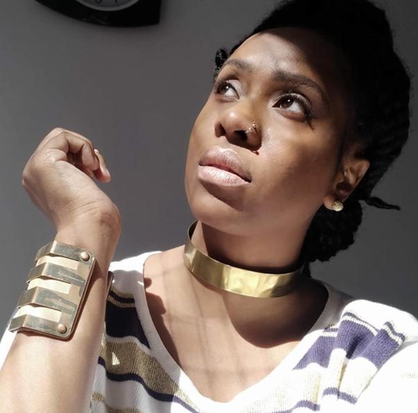 Foto mostra uma mulher negra com o rosto voltado para o sol, usando joias douradas