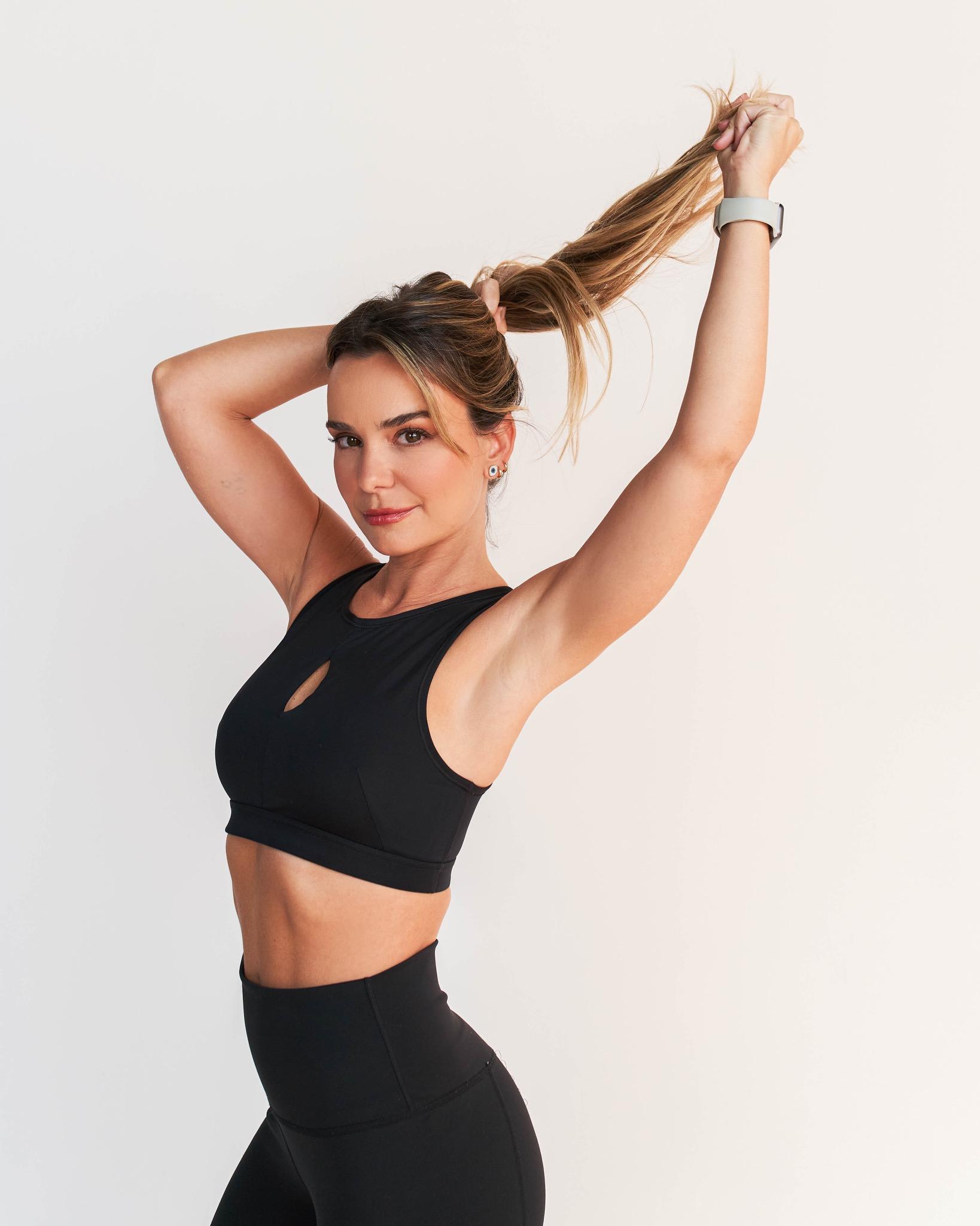 Foto mostra mulher com roupa de treino amarrando o cabelo