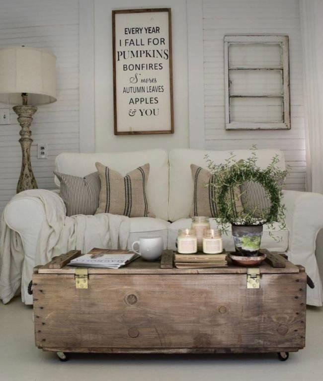A imagem mostra uma sala com sofá e um báu como centro de mesa