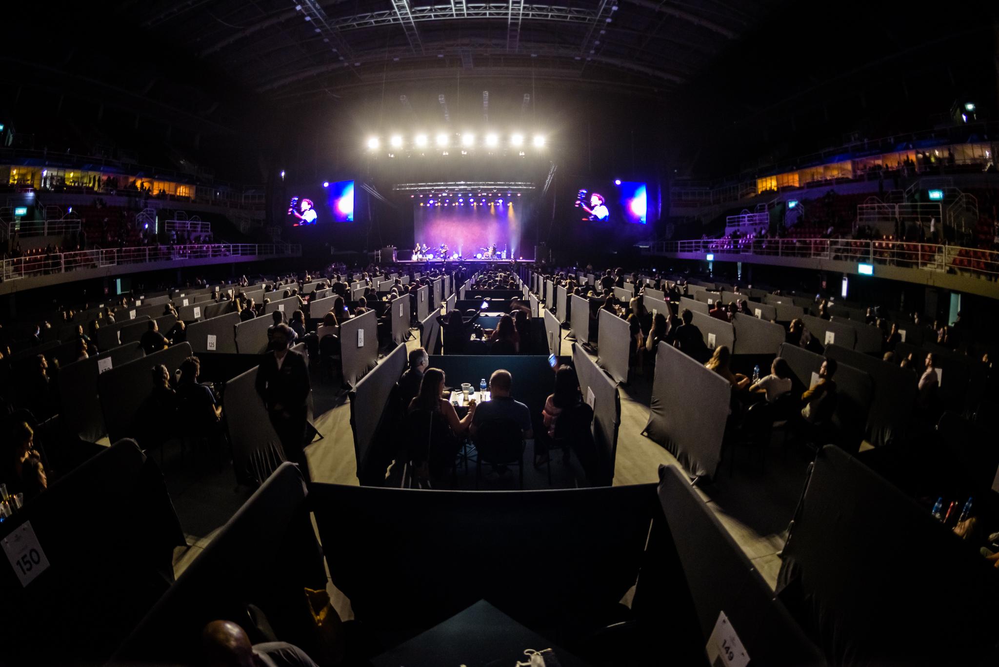 Jeunesse Arena com público acomodado em mesas e boxes separando cada uma delas