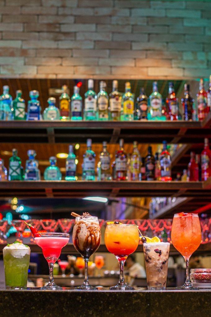 Drinques coloridos em balcão de bar