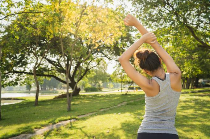 Healthy young Asian runner woman warm up the body stretching bef