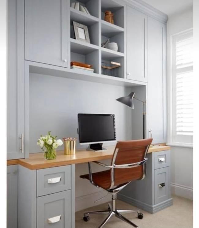A imagem mostra um home office. Em primeiro plano uma estante com mesa e em segundo plano uma cadeira de trabalho.