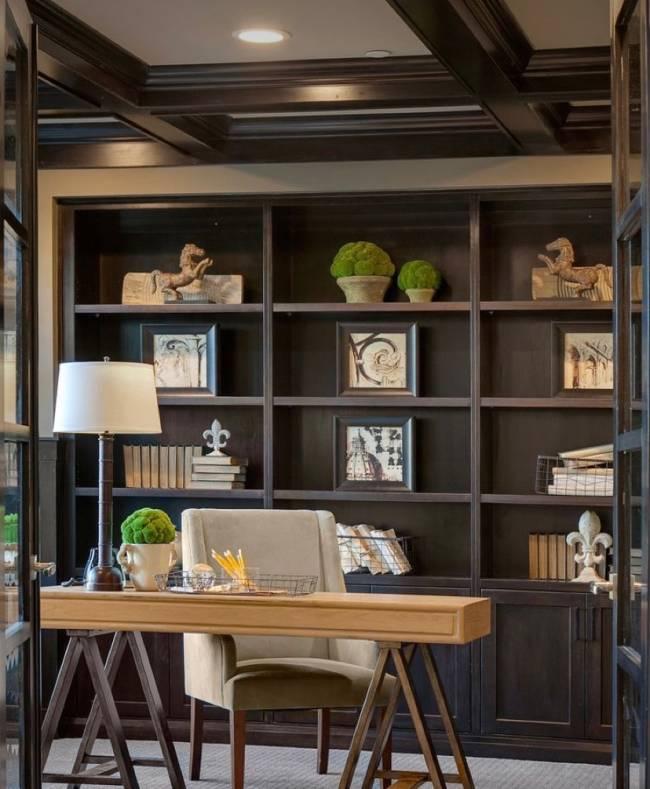 Imagem mostra um home office. Em primeiro plano uma estante e em segundo plano uma mesa com uma cadeira.