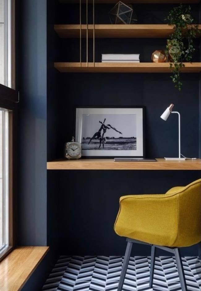 A imagem mostra um pequeno home office com parede azul e em segundo plano uma cadeira com estofado amarelo