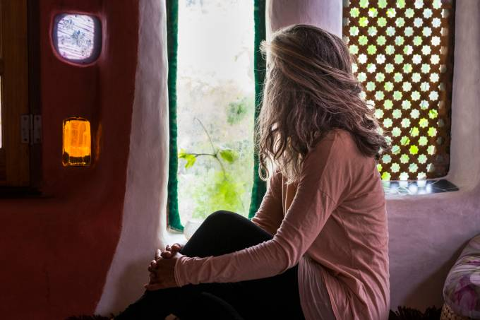 Lonely caucasian woman at home look through the window outdoor –