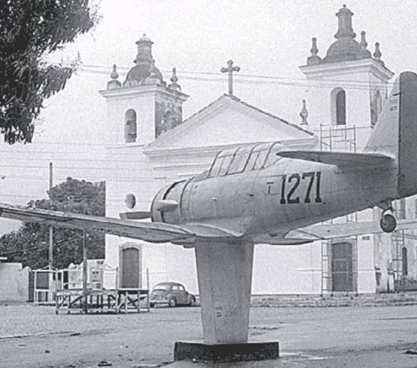 Foto do monumento de uma avião na frente da Igreja de Nossa Senhora do Loreto (1974)