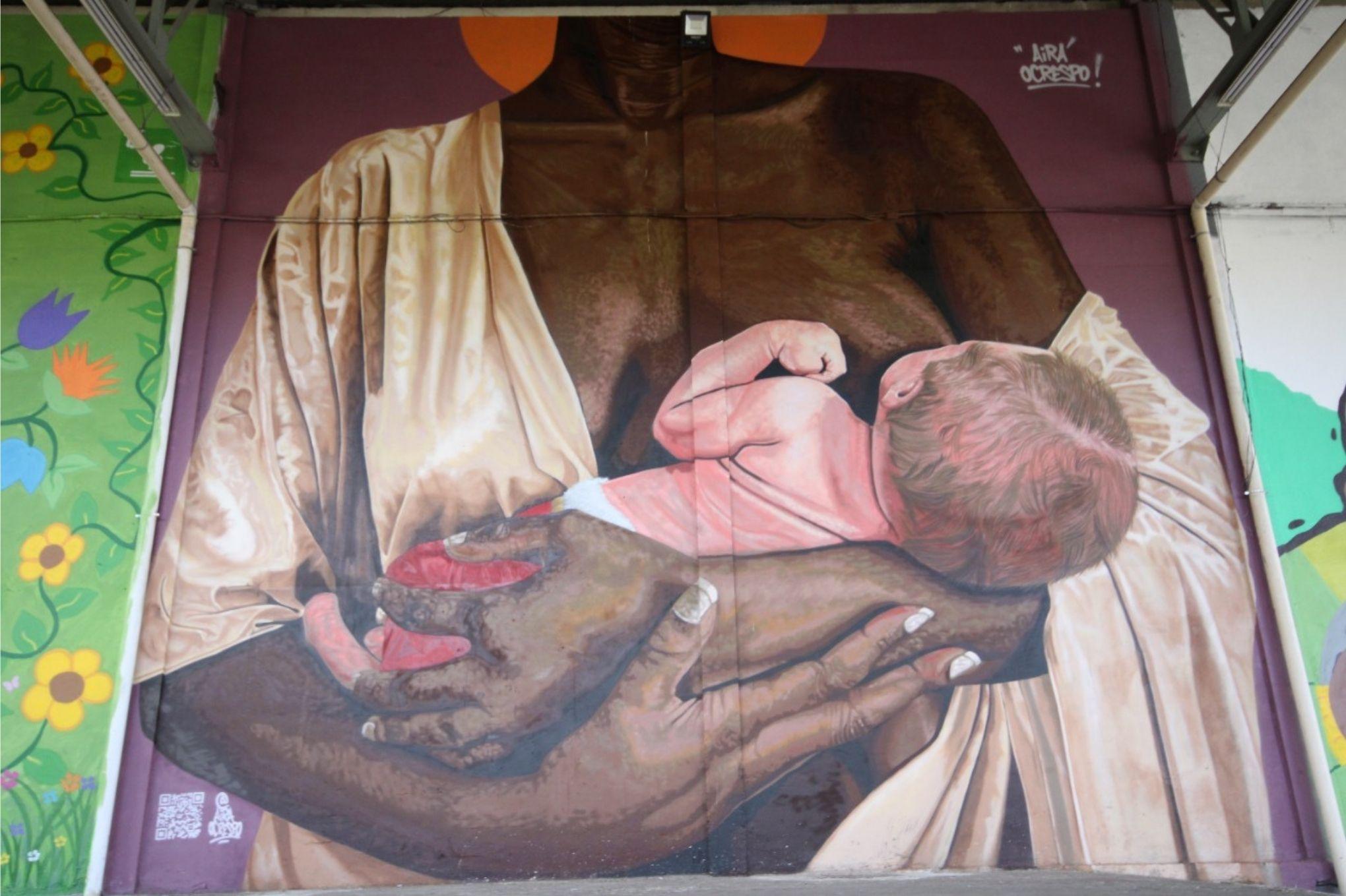 Obra em grafite retrata uma mulher negra amamentando um bebê branco.