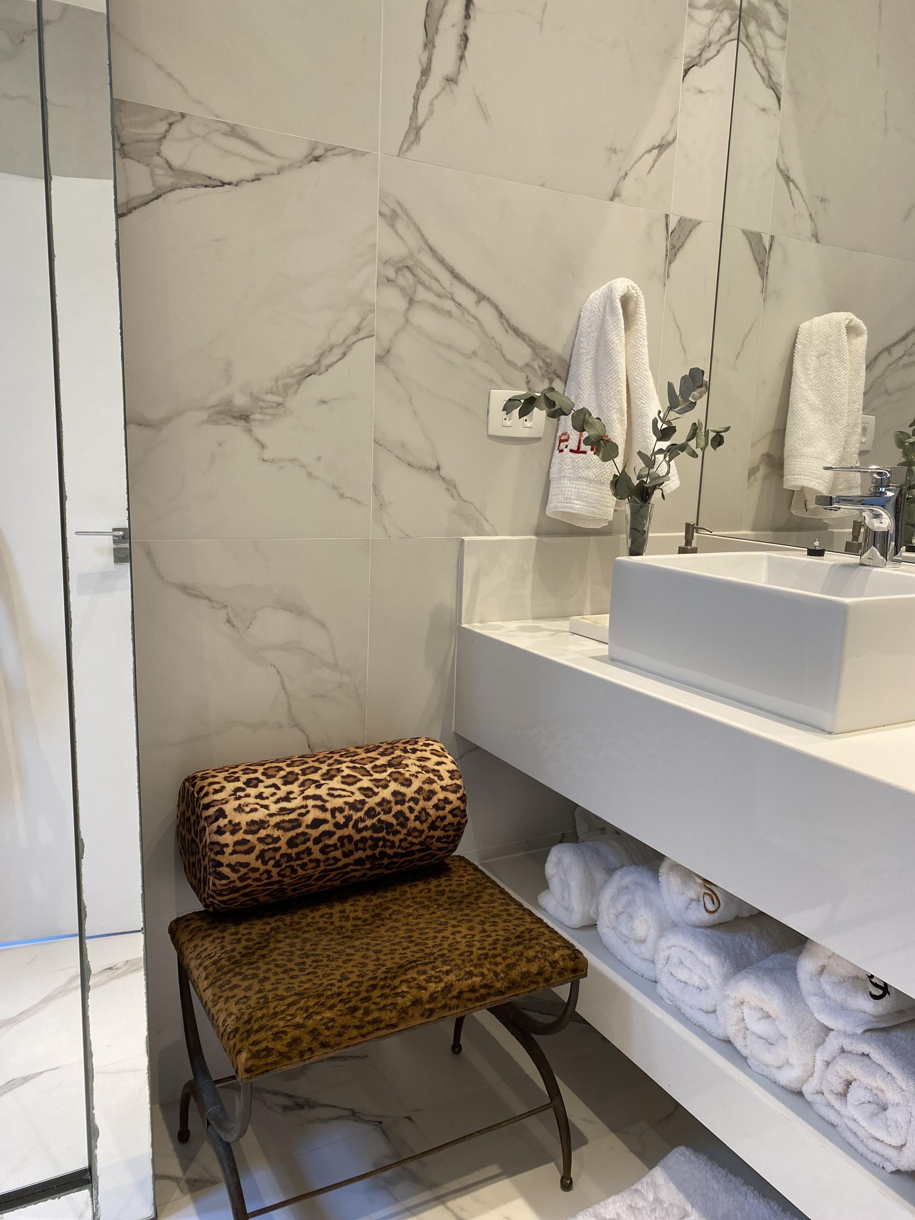 A imagem mostra um banheiro com banco de oncinha