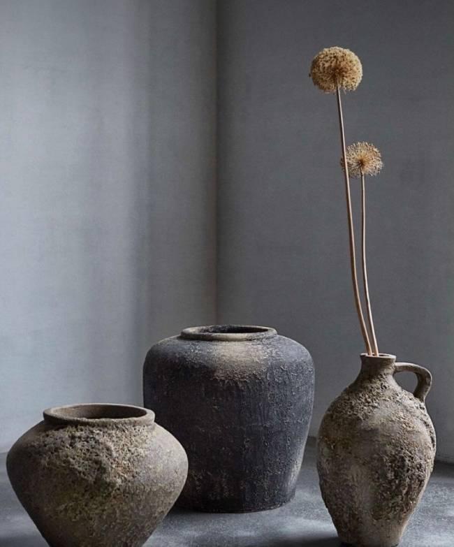 A imagem mostra vasos sem planta e um apenas com uma planta seca