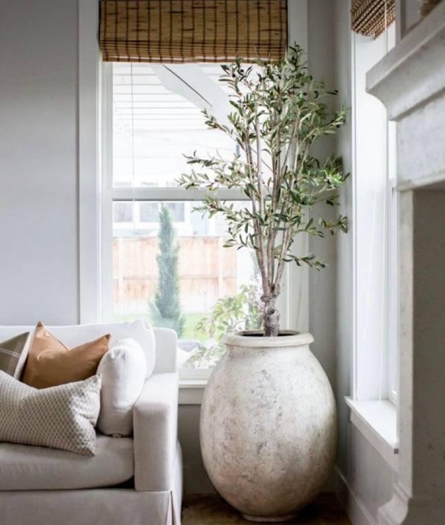 A imagem mostra um vaso ao lado de um sofá