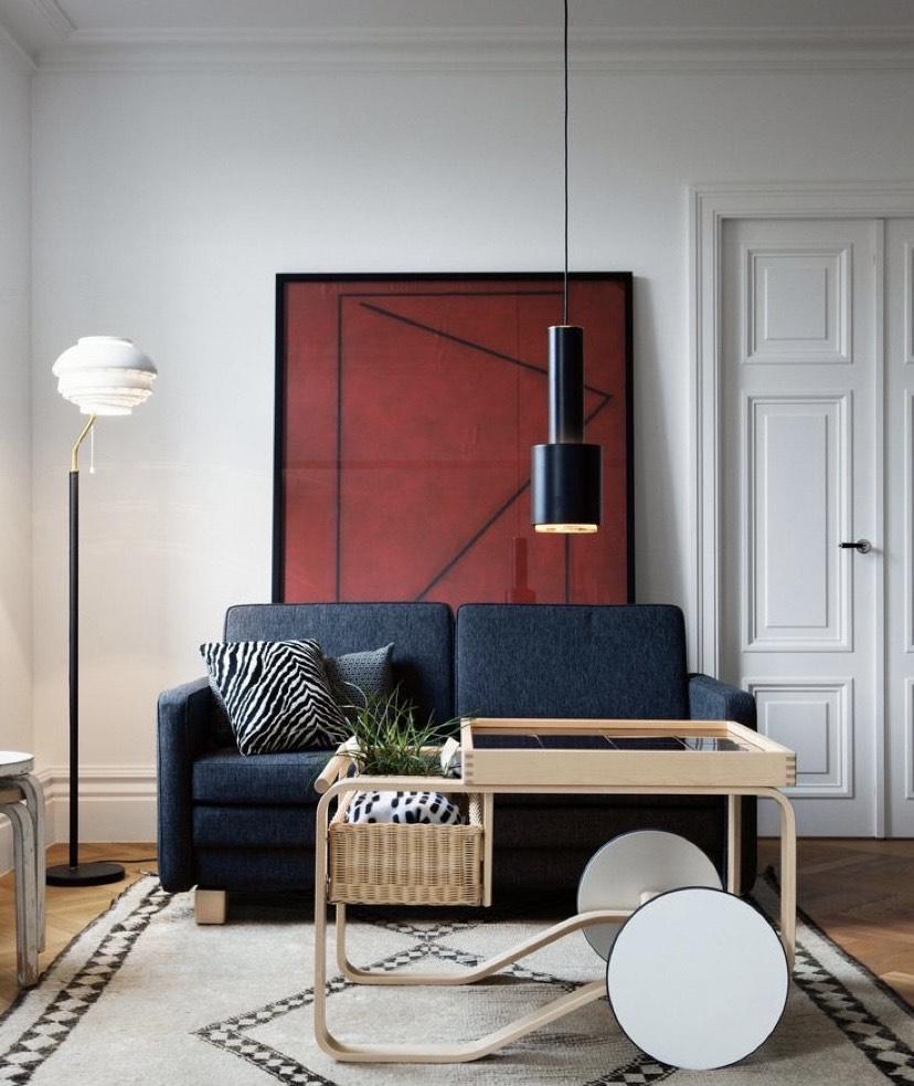 A imagem mostra uma sala com sofa, mesa de centro e almofadas
