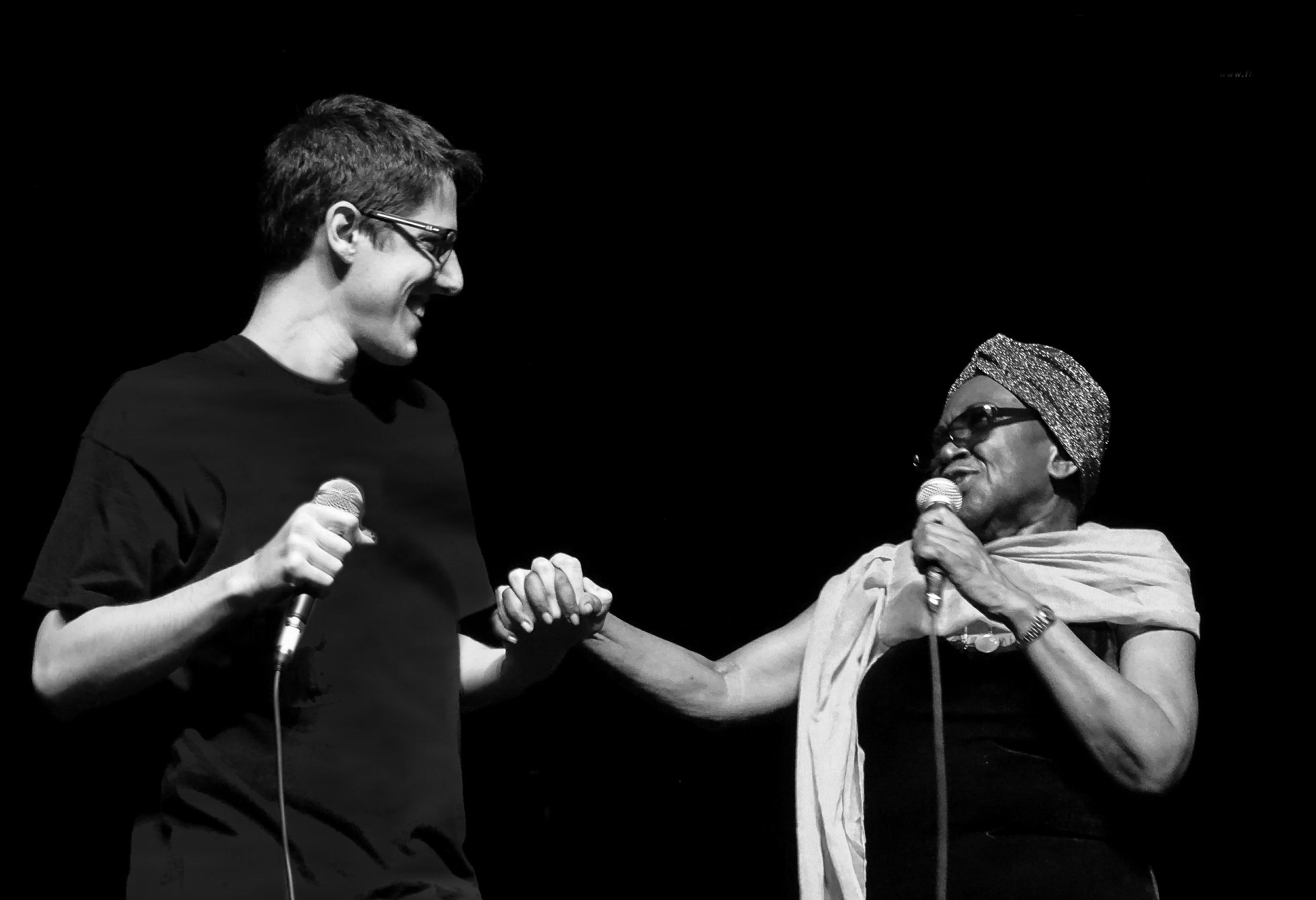 Cantores João Senise e Áurea Martins no palco, segurando microfones e dando as mãos um para o outro