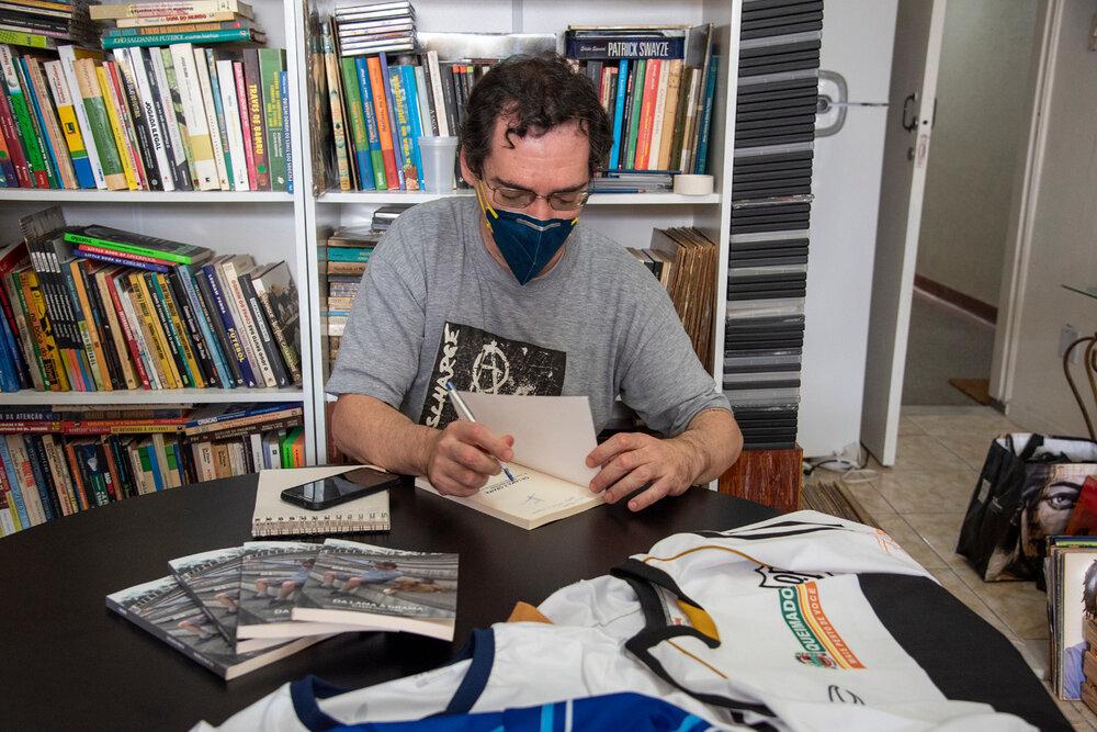 Kleber usa máscara facial e camisa cinza. Ele autografa um livro. Atrás dele há uma estante cheia de livros.