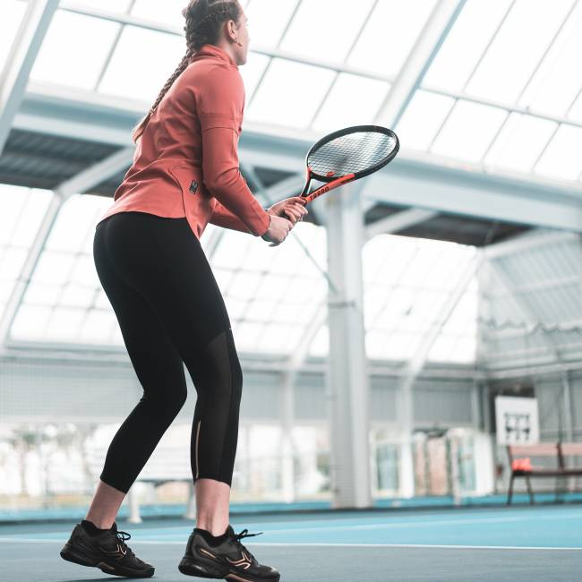 Foto mostra uma moça branca jogando tênis em uma quadra com piso azul