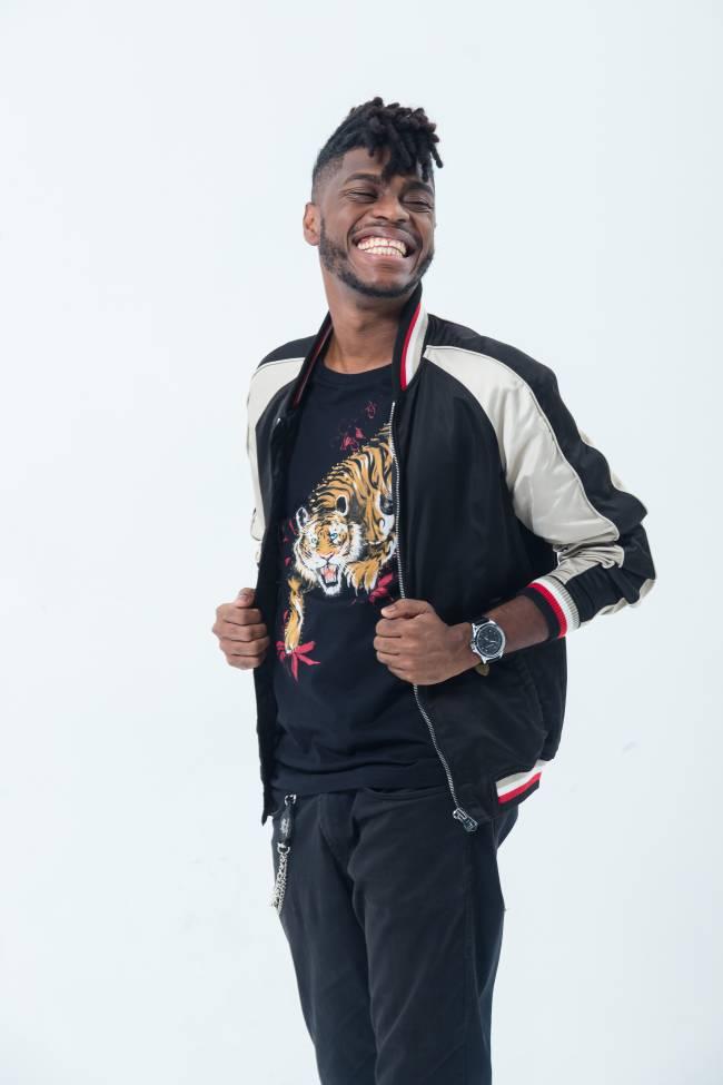 Yuri Marçal aparece usando uma blusa com um tigre estampado e uma jaqueta preto e branca com um grande sorriso no rosto