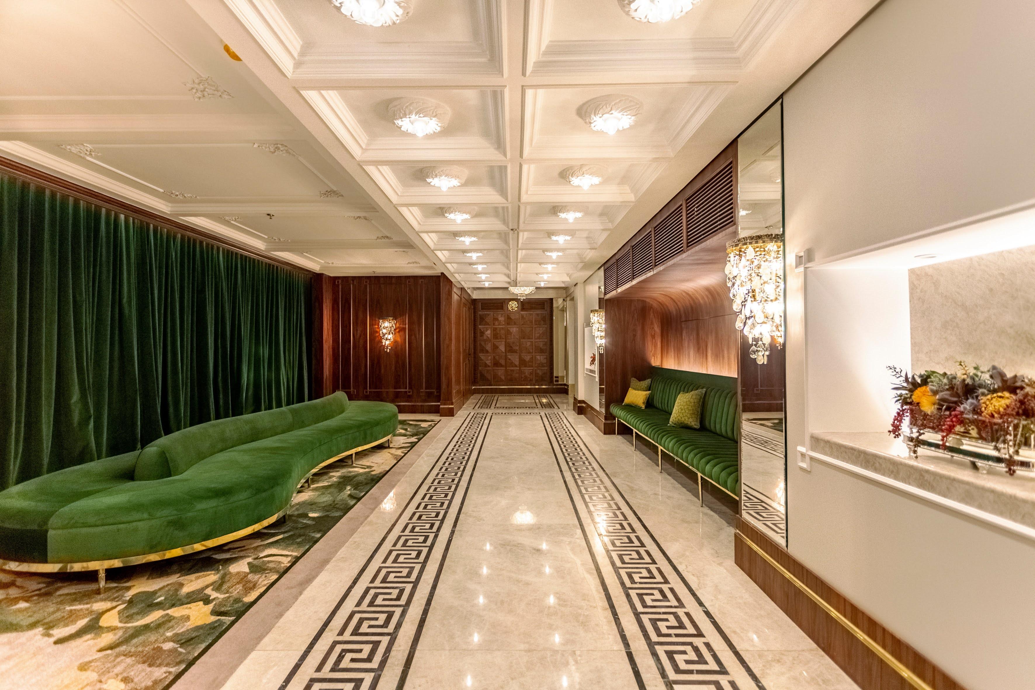 Foyer do Teatro Copacabana Palace, com lustres e sofá de veludo verde