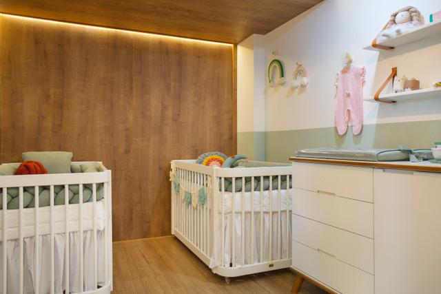 Um quarto de criança, com uma parede verde e outra em madeira, com dois berços brancos e um móvel de gavetas