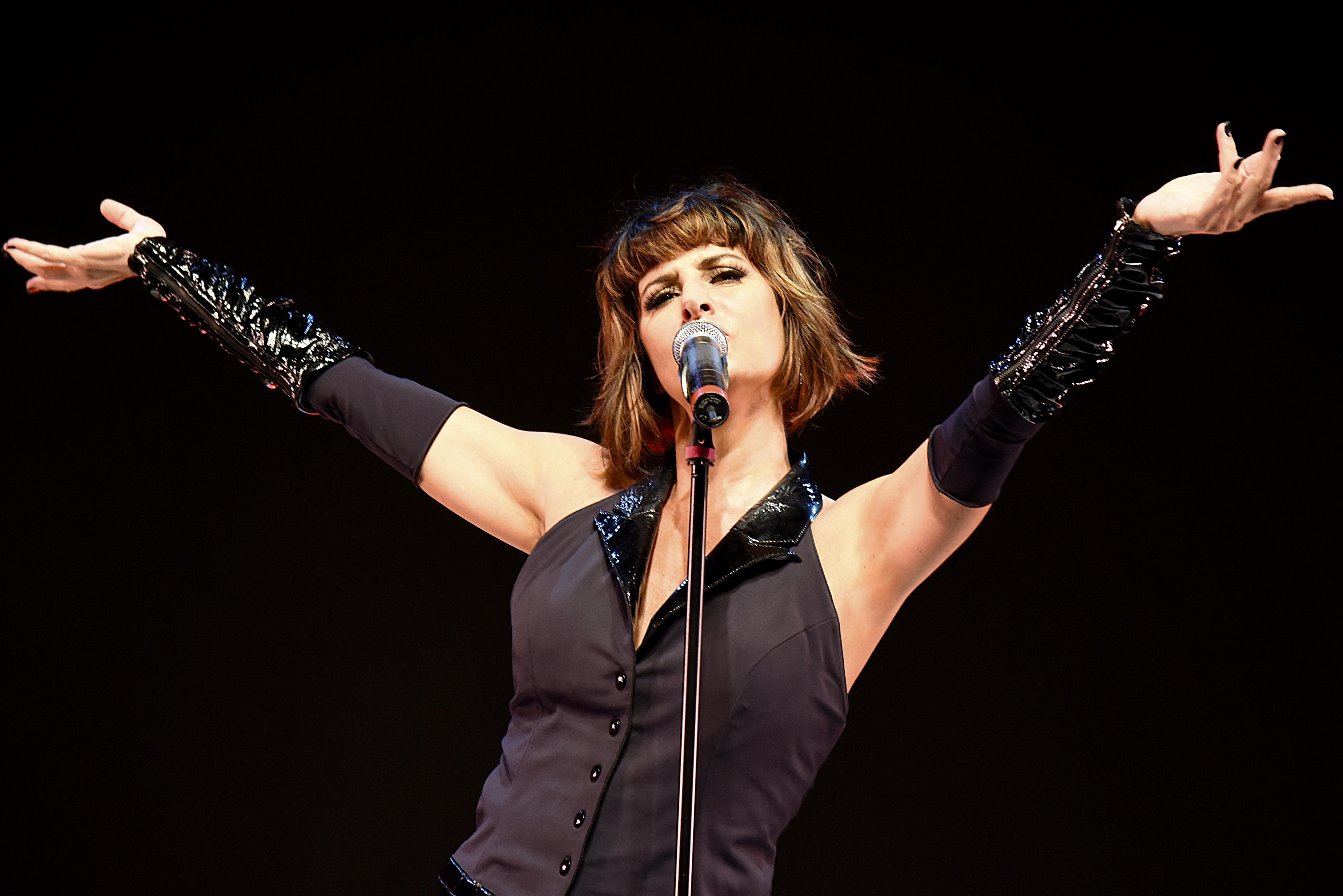A cantora Fernanda Abreu veste uma blusa preta sem alça e luvas pretas, com os braços para cima, enquanto canta no microfone