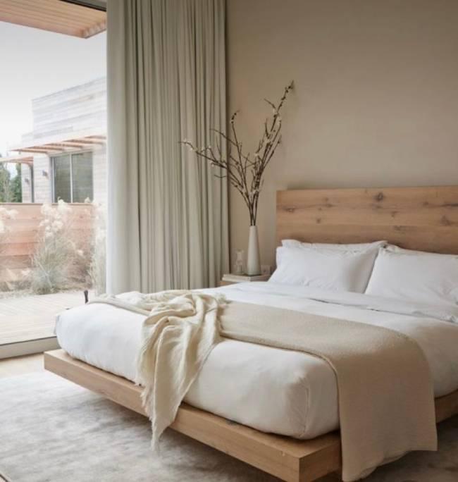 A imagem mostra um quarto com cabeceira de madeira