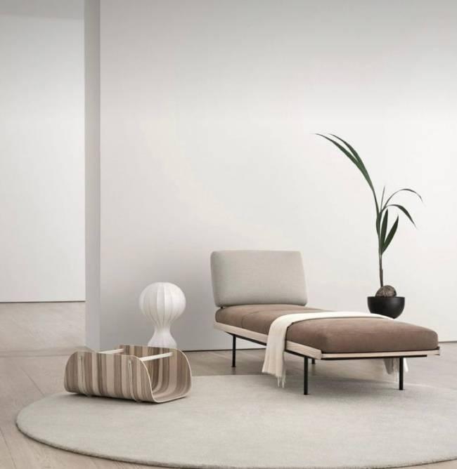 A imagem mostra uma sala com um vaso de planta, tapete e poltrona