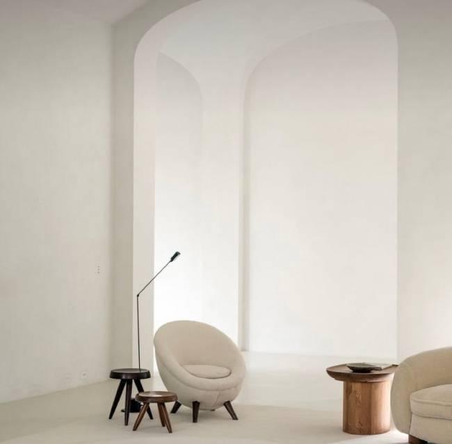 A imagem mostra uma sala com uma poltrona, banquinhos e uma luminária de piso