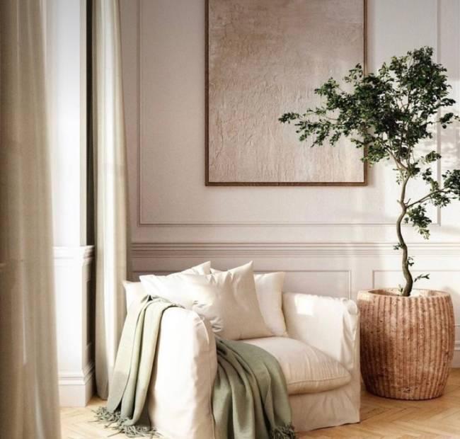 A imagem mostra uma poltrona com manta e um vaso com planta