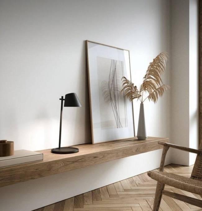 A imagem mostra uma bancada com madeira clara, quadro apoiado e uma luminária de mesa