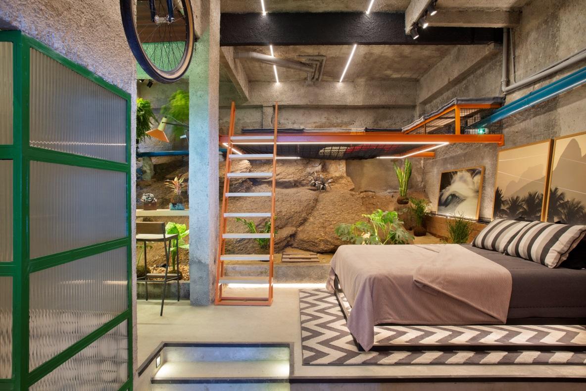 Um studio tem como uma das paredes uma grande pedra natural. Uma cama com lençol zinza está à direita e uma escada laranja leva para um mezanino à esquerda.