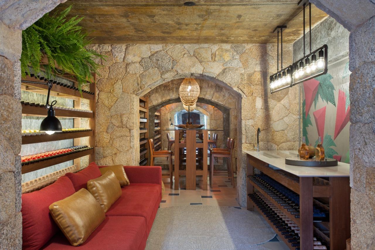 Uma dega de vinho em pedra tem um sofá vermelho à esquerda com almofadas de couro e uma bancada branca à direita