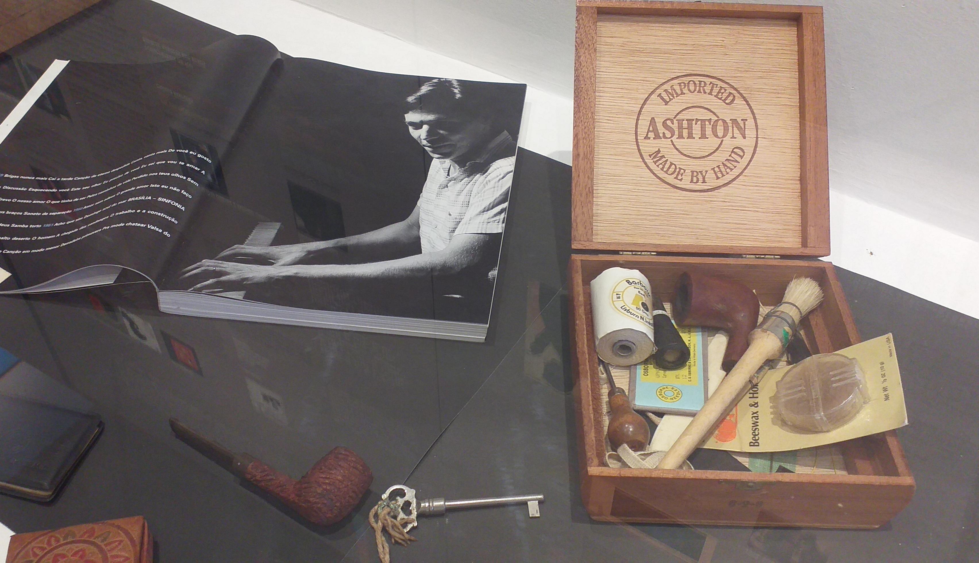 Imagem mostra artefatos de Tom Jobim, como um caximbo, uma caixa e uma foto do músico
